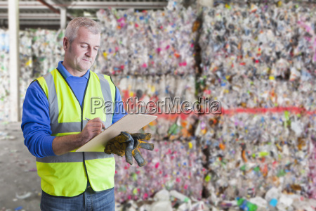 male worker with clipboard checking waste