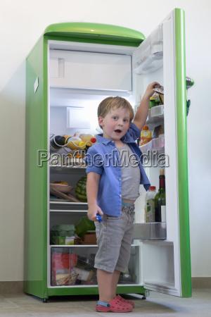 portrait of young boy raiding refrigerator