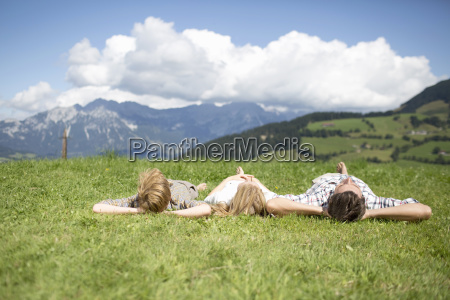 father and children lying on backs