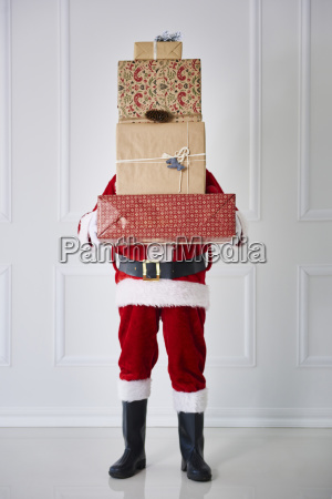 santa claus holding stack of christmas