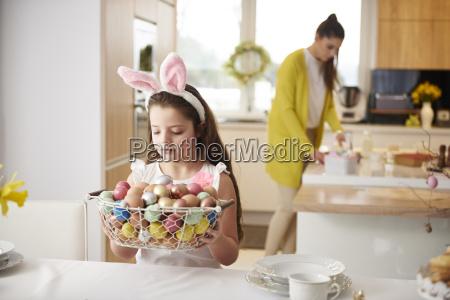 girl placing basket full of easter