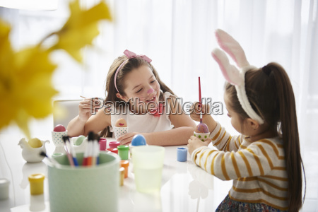 sisters sitting at table painting easter