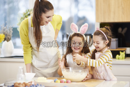 happy mother and daughters baking easter