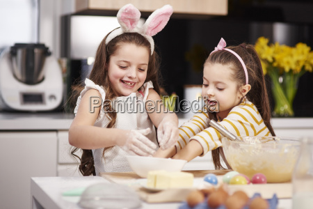 two sisters having fun baking easter