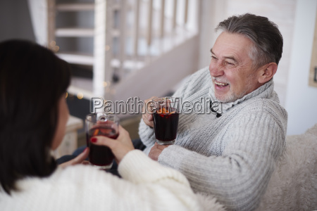happy mature couple with hot drinks