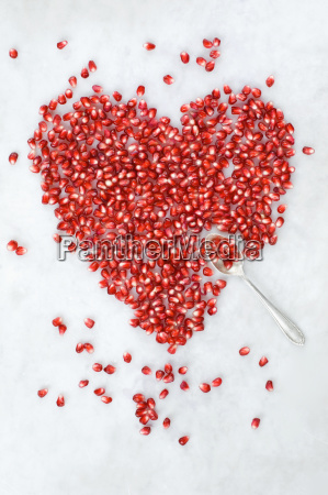 heart shaped of pomegranate seeds on