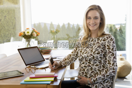portrait of smiling pregnant woman working