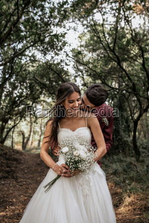 groom kissing smiling bride in forest