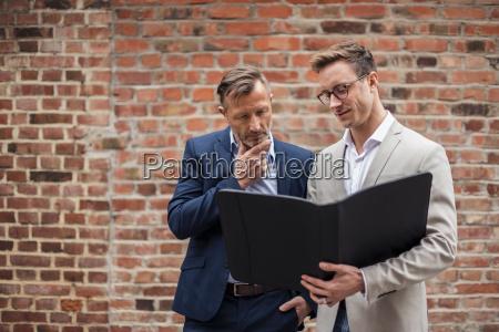 two businessmen sharing folder at brick
