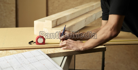 worker marking wood with pencil tape