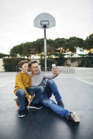 father and son sitting on basketball