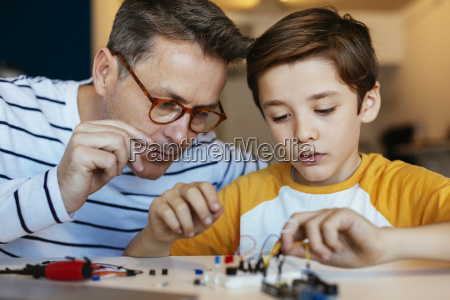 father and son assembling an electronic