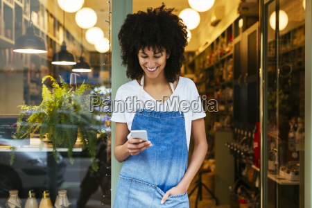 smiling woman using cell phone in