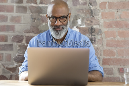portrait of smiling businessman using laptop