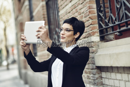 smiling young businesswoman taking selfie with