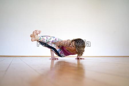 mature woman practicing yoga on floor