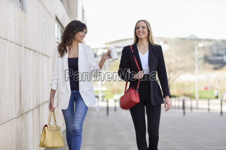 two smiling businesswomen with handbags and