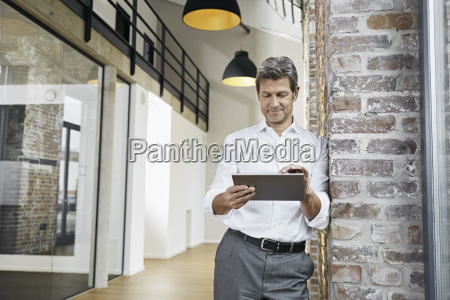 portrait of mature businessman using tablet