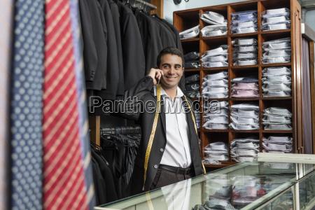 smiling elegant tailor talking on phone