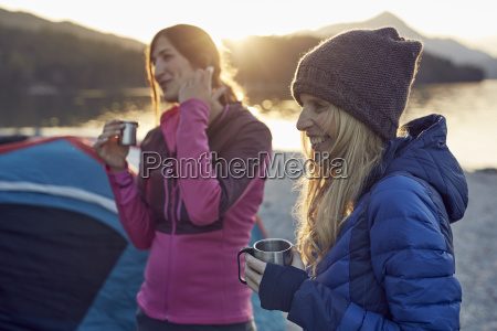 two female friends at tent holding