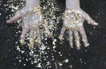 palms of girl covered with gold
