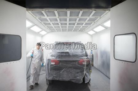 auto painter painting a car inside