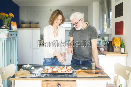 mature couple preparing a pizza in