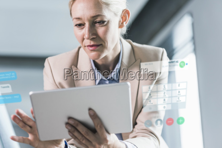 businesswoman sitting in office using digital