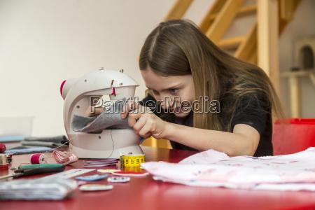 smiling girl using sewing machine