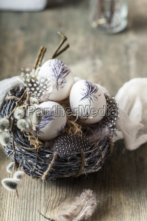 painted easter eggs in nest with