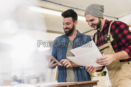 two happy men with tablet looking