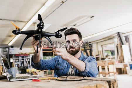 man working on drone in workshop