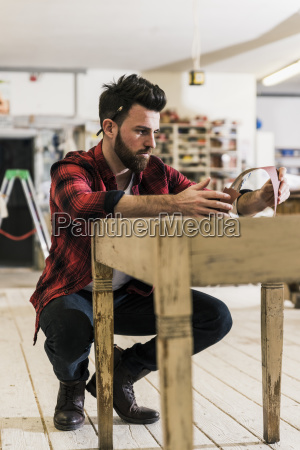 man treating wood in workshop with