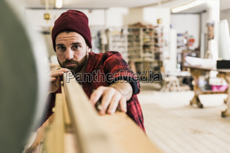 man examining wood in workshop