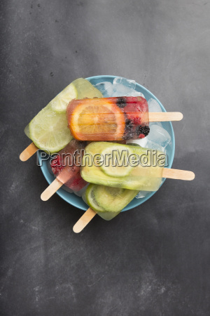 various fruit popsicles on bowl with