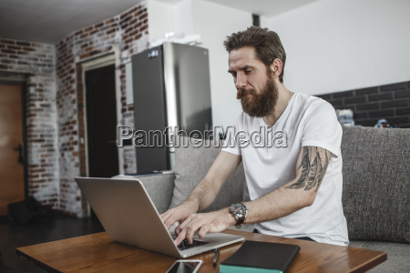 bearded man sitting on the couch