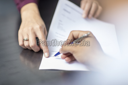 close up of signing a document
