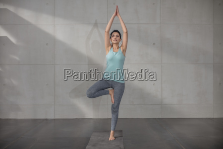 young woman doing yoga exercise in