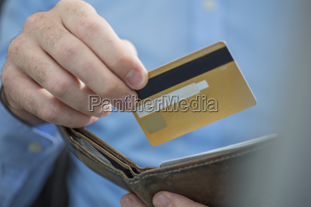 mans hands holding credit card and