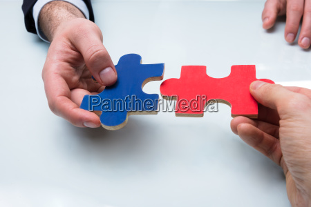 two businesspeople holding jigsaw puzzle