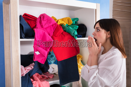 shocked woman looking at scattered clothes