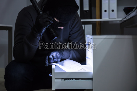 thief stealing document from drawer