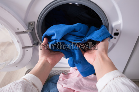 womans hand putting blue cloth into