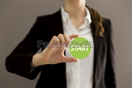 young businesswoman holding virtual button start