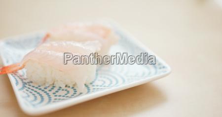 putting shrimp sushi on the plate