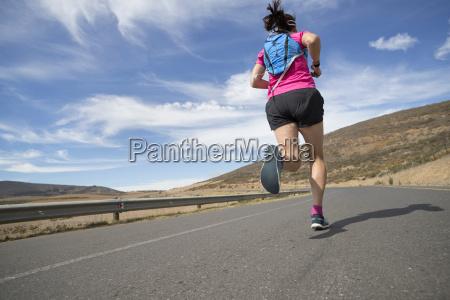 female runner running on open road