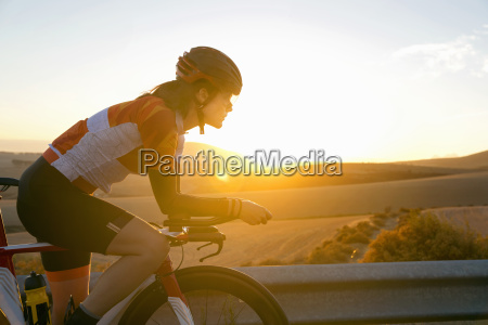 female cyclist riding race bicycle on