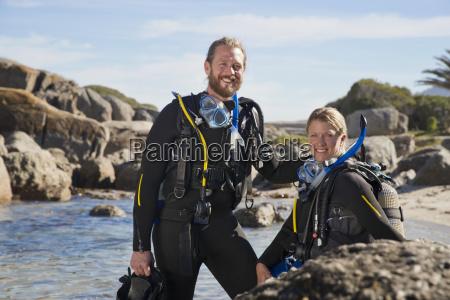 couple in wetsuits going ocean scuba