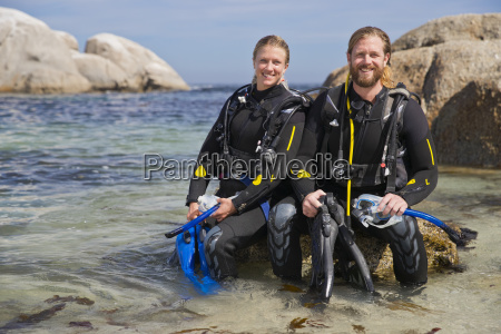 couple in wetsuits smiling at camera