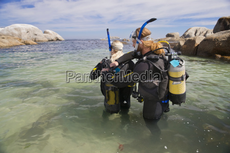 dive instructor checking equipment of fellow